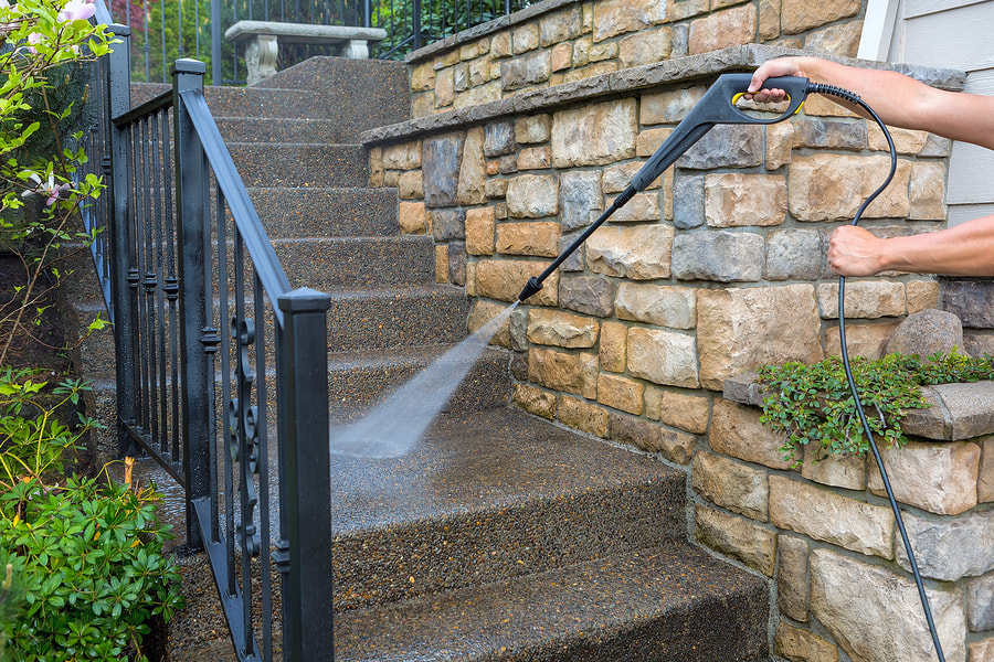 man pressure washing stairs